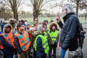 Een gids geeft uitleg aan een klas tijdens de winterwandeling