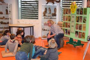 Een gids geeft uitleg aan een klas binnen in het Natuur- en Milieucentrum