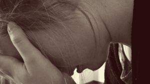 meisje met haar hoofd tussen haar handen