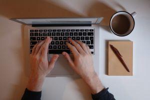Handen typen op het toetstenbord van een laptop.
