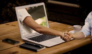 hand die uit de computer komt en een hand geeft