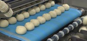 balls of dough on a conveyor belt