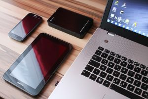 Different types of mobile devices lie on the wooden table.