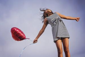 Meisje met een rode ballon in de vorm van een hart