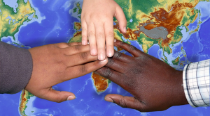 hands of children of different origins on a globe