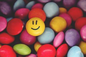 Colored Smarties, a smiling face is drawn on one of the Smarties