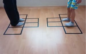 Snapshot uit video: leerlingen staan in vakjes op de vloer
