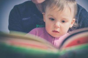 Peuter zit bij een persoon op schoot en kijkt in een boek.