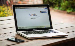 En laptop staat op een tuintafel. Op het scherm staat de zoekmachine van Google.  Naast de laptop ligt een zwarte smartphone.