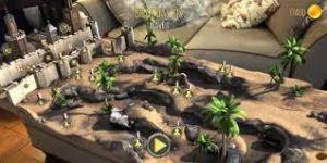 Het virtuele spelbord staat op een echte salontafel. Het kasteel dat je moet verdedigen staat in een woestijnachtig gebied.