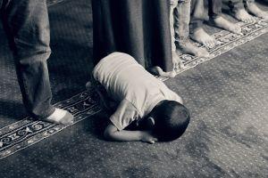 een jongen bidt knielend