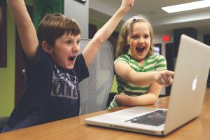 Two children cheering at a laptop