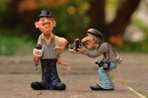 two figures: one is a journalist, the other is a photographer