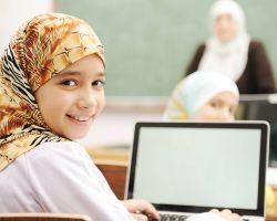 Meisje met hoofddoek aan een laptop