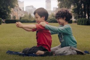 still from the film Aatos and the world. two boys are sitting on the grass.