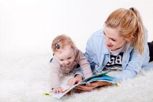 mama en kind liggen op de mat en lezen een boekje