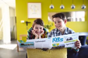 two boys look together in the Kits newspaper