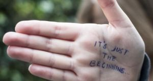 """op de handpalm staat geschreven """"it's just the beginning"""""""