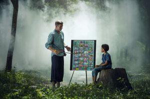leraar geeft les aan leerling in een bos