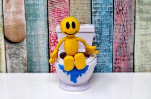 Geel popje zit op het toilet