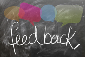 op een zwart krijtbord staat het woord feedback geschreven. Er staan gekleurde tekstballonnetjes boven het woord feedback.