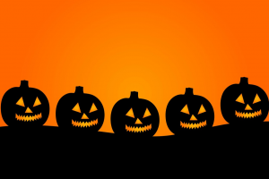 black silhouettes of halloween pumpkins on an orange background