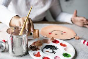kind schildert met verf op verfpallet