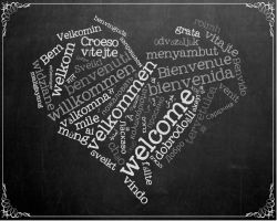 heart with welcome in different languages on chalkboard