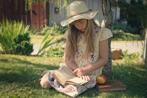 girl reads a book in a garden