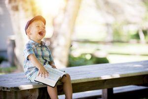 Jongen die lacht met het lezen in een boek