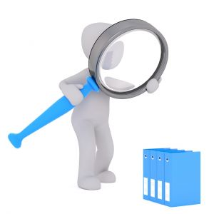 male viewing with magnifying glass files