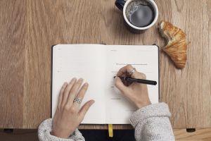 Iemand schrijf in een schrift aan een tafel