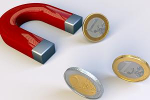 een magneet trekt geldstukken aan