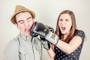A woman boxing a man with boxing glove