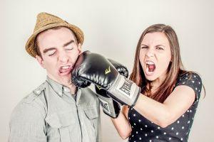 Een vrouw die een man bokst met bokshandschoen