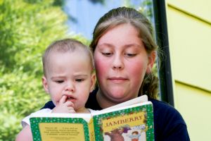 Mom and toddler read in a book