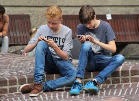 Two teenagers sit side by side on a wall with their smartphone in hand.