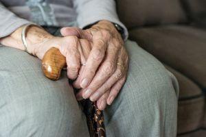 handen van een oude persoon houden een wandelstok vast