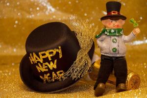 Een mannetje naast een hoed. Op de hoed staat 'happy new year'