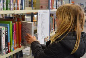 kind zoekt boek in bib