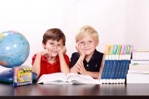 Twee jongens kijken in een boek. Naast hen staat een wereldbol.