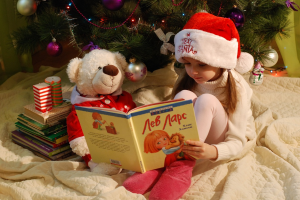 Meisje met kerstmuts leest voor aan haar knuffelbeer. Ze zitten bij de kerstboom.
