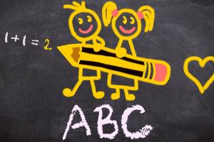 Een meisje en een jongen getekend op een bord. Onder de kinderen staat ABC