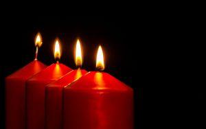 vier rode kaarsen op een rij