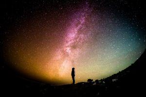 silhouette van een jongen met op de achtergrond de melkweg
