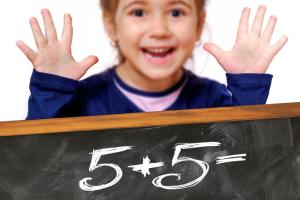 kind staat achter een bord waar een optelling opstaat