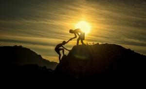 persoon helpt een andere de berg op