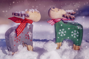 twee houten rendieren in de sneeuw