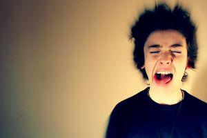 jongen schreeuwt en steekt zijn tong uit