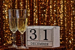twee glazen champagne naast een kalenderblok dat 31 december aangeeft